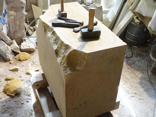 Sandsteinblock mit Bearbeitungsspuren. Erste Bearbeitungen sind mit Sprengeisen und Fäustel gemacht. Steinmetzwerkzeug liegt auf dem Stein.