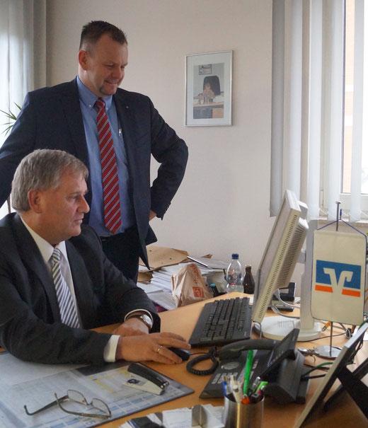 Am Rechner werten die Volksbank-Vorstände Martin Trahe (links) und Stefan Hildebrand einige Bankdaten aus. Foto: Alpha-Report