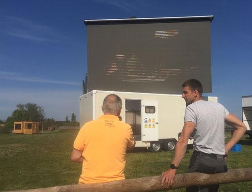 Betreiber Carsten Heidel (rechts) justiert die riesige LED-Wand auf dem Platz vor dem Pareyer Erlebnisdorf für das Autokino 2020. Foto: Alpha-Report