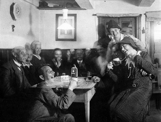 """Hervorragende Stimmung im kleinen Schankraum beim Gastwirt Franz Bruder.  Auf dem Tisch der Verursacher: """"August mit dem Schlips"""""""