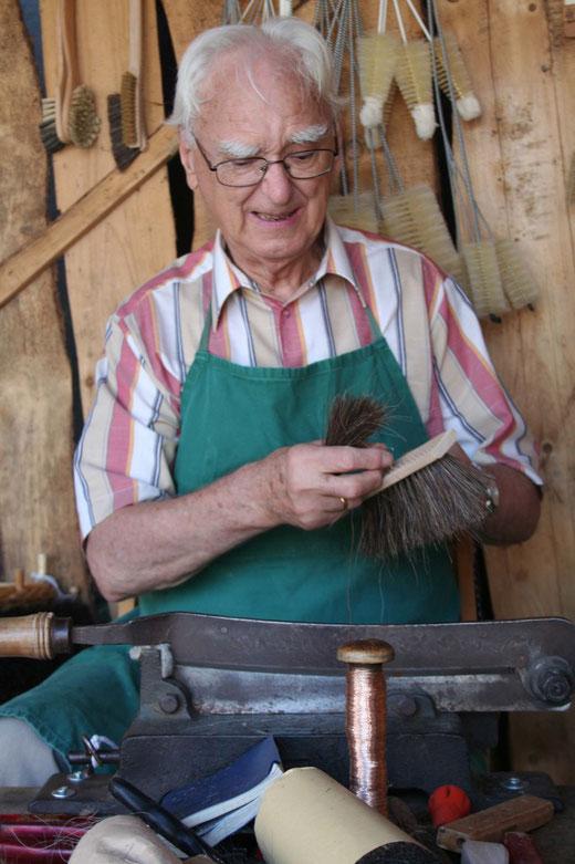 Ferdinand Rentmeister bei der Arbeit. Das Foto entstand auf einem Markt, dort wo er nicht nur seine Waren anbietet, auch sein Handwerk vorstellt.