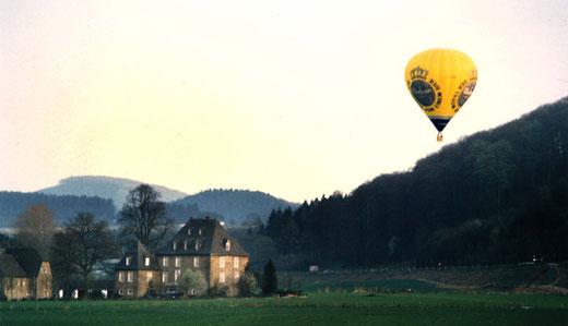 Ein moderner Heißluftballon auf seiner Fahrt über dem Wennetal bei Gut Wenne