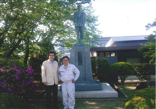 理事長 梅沢先生(左)と私(右) 後ろの銅像が創始者 梅沢 義三 翁です。翁「西山君、遠い所、当学園にお越し頂き、ありがとう!君の事は、孫からよく聞いておる。うん、うん。国の為に頑張ってくれよ。私は、天国で君と孫の国家への貢献を見ているぞ。うん、うん。」