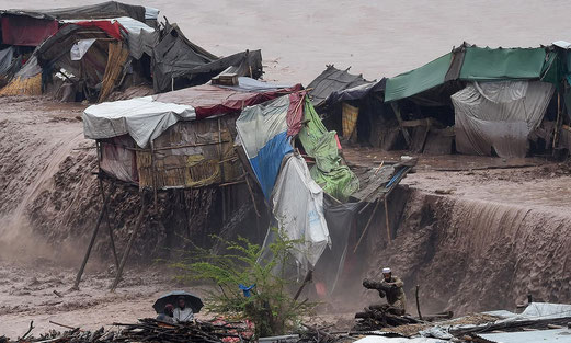 Flood waters rush through a Pakistani market area as vendors and residents look on. —AFP