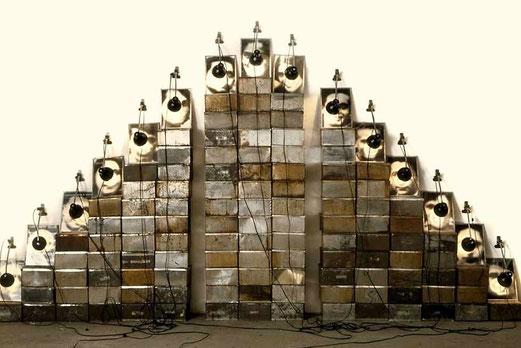 Autel Chases, 1988 - OEuvre composée de 112 boîtes à biscuits, 15 lampes et 15 photographies noir et blanc 230 cm x 400 cm. Chaque photographie : 30 cm x 24 cm. Chaque boîte : 23 cm x 23 cm x 13 cm. © © Inventaire 89068, FNAC