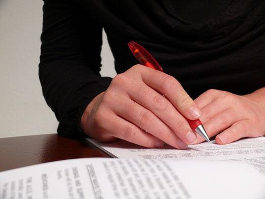 Korrektur eines Textes durch Frau mit Kugelschreiber in der Hand
