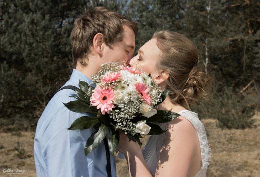 Braut und Bräutigam Küssen sich und halten den Brautstrauß vor sich
