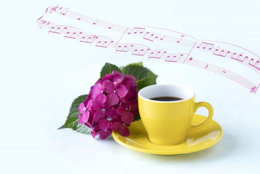 花柄の包装紙につつまれたギフトボックス。小さなハート形のギフトボックスに詰められたアップルパイ。コーヒーの入ったカップ&ソーサ。ブルーベリーの小枝。