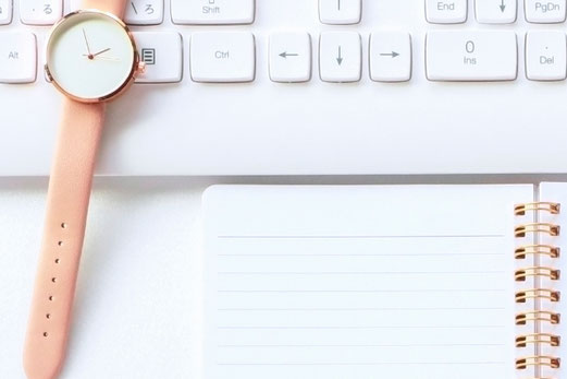 ノートパソコンの傍らに広げられたノート、マグカップ。