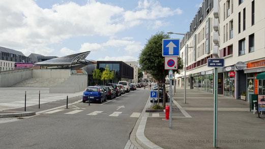 La rue Nicolas Bouvier, située au Nord de la Médiathèque. Sur la gauche de la photo, la piste cyclable qui lone la médiathèque. Sur la droite, le large trottoir qui longe les commerces