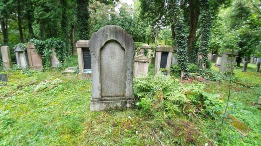 Das Bild zeigt einen Grabstein und eine leere Stelle daneben. Diese leere Stelle ist das nicht genutzte Grab von Karl Bacharach. Er kaufte es vor seiner Flucht aus Nazideutschland. Weder im Leben noch im Tod kehrte er je in seine Heimat zurueck.