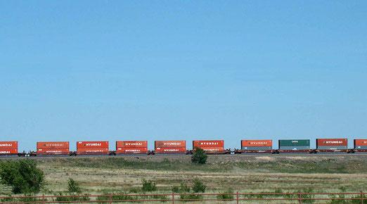 Parallel zu uns fahren kilometerlange Güterzüge mit Kompositionen bis zu 120 Wagen.