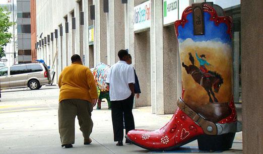 Der wohlgenährte Herr links zieht achtlos am überdimensionalen, hübschen Cowboystiefel vorbei.