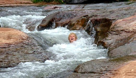 Die Mutigen lassen sich auf den glitschigen Felsen im Wasser hinuntertragen (slide = gleiten, rutschen)