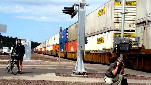 Williams: (Zahlen) Der Biker links zählt 125 Güterwagen oder ca. 2 km Länge des Güterzuges, gezogen von 3 Loks. Mein Freund (rechts) ist stets mit der Kamera schussbereit: Am Ende der Reise werden es wohl gegen 6000 Bilder sein.