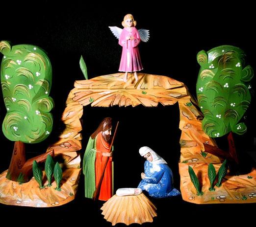 14. Dezember . Russische Holzkrippe mit zwei Bäumen, einem Engel und der Heiligen Familie, Jesuskind auf Stroh. 18 Teile, zusammensteckbar, mit Glanzfarben bemalt, Höhe 22 cm.