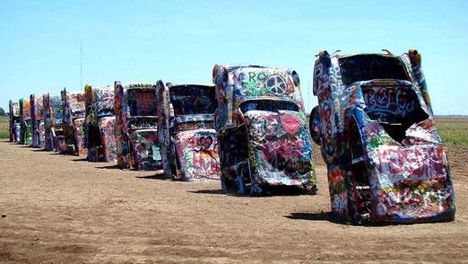 Es sind zehn bunt bemalte Cadillacs in einer Linie im Boden eines Maisfeldes eingegraben.