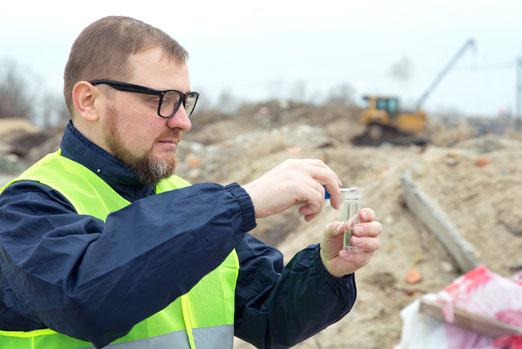 Mann entnimmt Bodenprobe auf Baustelle