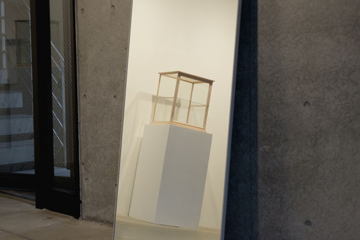吉川和人さんによる木製の什器を鏡越しに