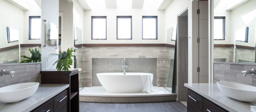 Grey Limestone, Gray porcelain tiles, white tub and vessel sinks in a contemporary bathroom