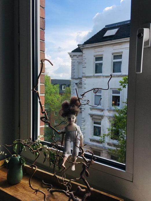 Puppe auf Fensterbrett, vor Fenster