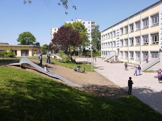 Pausenhof mit Ruhe- und Bewegungszonen sowie einem  Blick auf den Mittagsbetreuungsbau