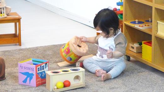 ピッコロコース(6ヵ月~1歳) モンテッソーリ活動で、いろいろな教具を触って確かめている乳幼児。