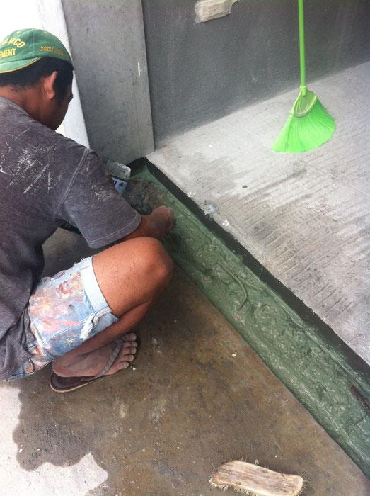 Mann streicht Flüssigkunstoff auf Türschwelle im Eingangsbereich