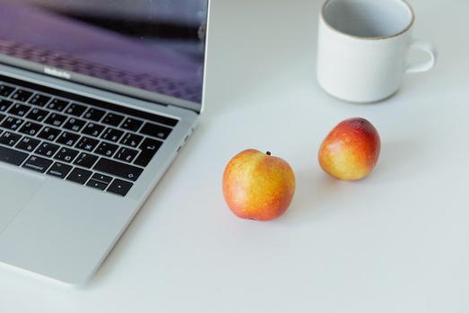 パソコンのキーボード。ピンクのフレームの眼鏡。メモパッドとゴールドのボールペン。
