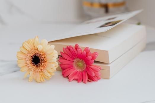 ピンクのノートパソコン、眼鏡、イヤフォン、ボールペン、メモ帳。