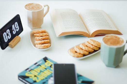 資料とノートパソコンを広げてチームミーティング中。テイクアウトコーヒーを飲みながら。