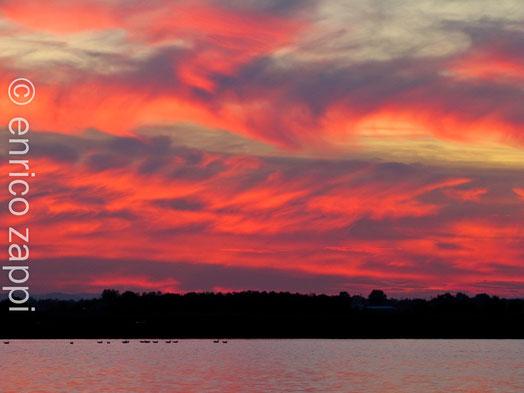Il riverbero rosso del sole appena tramontato si riflette all'orizzonte sulle grigie nubi battute in quota da un veemente vento che le fa mulinare creando un paesaggio meraviglioso e surreale. ( Saline di Cervia (RA) 07.10.12)