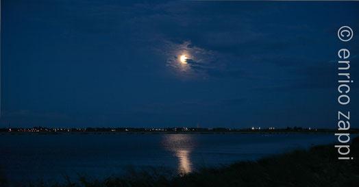 5.5.2012. La Superluna, ormai alta nel cielo si staglia sopra Cesenatico e si rispecchia in uno dei chiari delle Saline di Cervia.