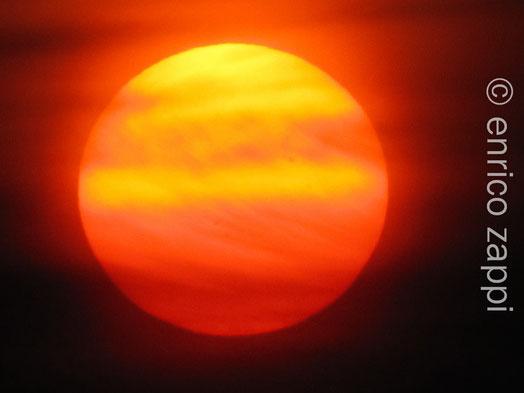 Sole al tramonto fra la foschia all'orizzonte