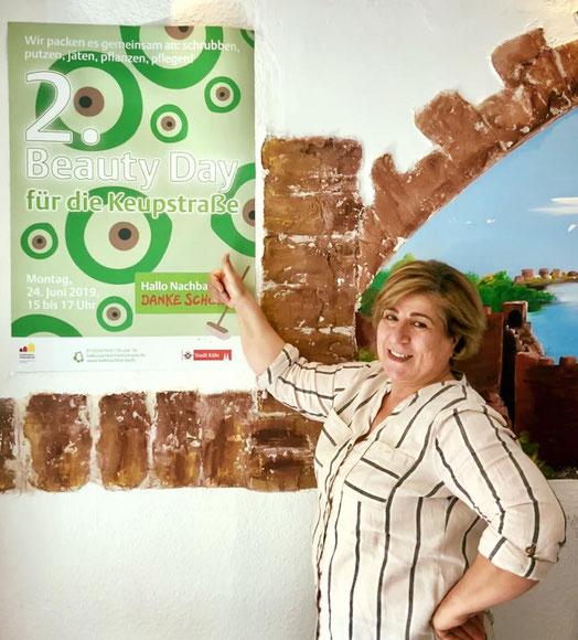 """Elif Tatli Agkün vor dem Plakat """"Zweiter Beauty Day für die Keupstraße"""""""