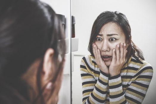 鏡に映る自分の老け顔に驚く女性