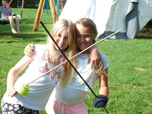 Zwei Mädchen halten sich im Arm und haben in der anderen Hand einen selbstgebauten Degen. Beide lachen in die Kamera.