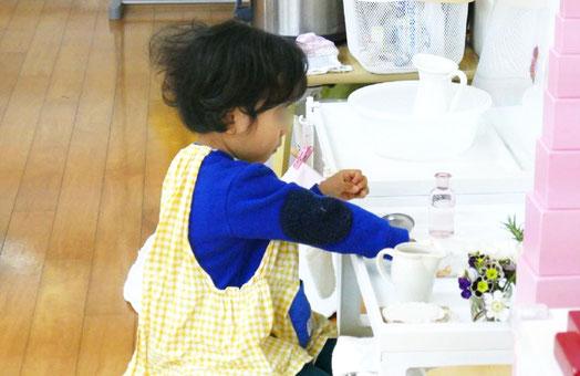 母子分離をして活動する2歳児が、お花をいけるお仕事に夢中で取り組んでいます。