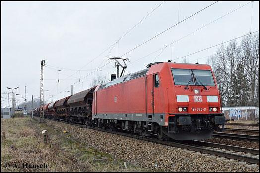 Die DB besitzt eine Vielzahl von 185ern. Eine davon ist 185 320-9, die am 18. Februar 2015 mit ihrem Güterzug durch Leipzig-Thekla fährt