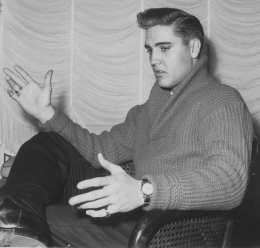 """Elvis wird im Hotel Grunewald interviewt und bittet die Fotojounalistin: """"Baby, watch the beer bottles, please!"""" (Die Bierflaschen ihrer Journalisten-Kollegen sollten bitte nicht mit ins Bild.) Sammlung ONLINE-MUSEUM BAD NAUHEIM, Foto: Boelke, Bad Nauheim"""