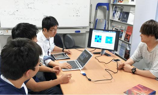 研究室で若手教員と学生のディスカッションです。ナノ微粒子集合体に光が当たった時の様子をシミュレーションした結果について議論しています。