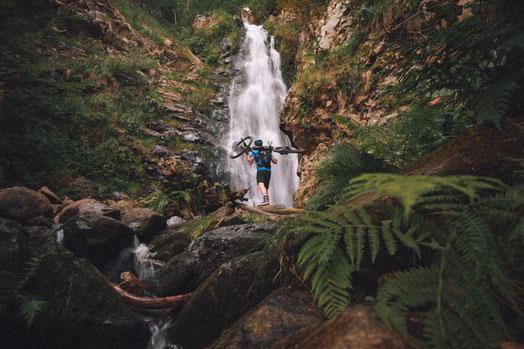 Ein Mann schultert sein Cannondale Trail Neo am Wasserfall