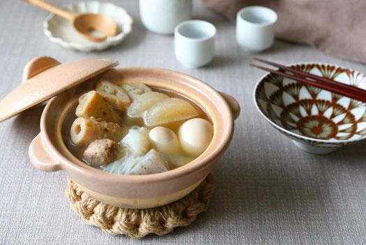 デスクのノートパソコン。手帳のうえに置かれたリーディンググラスとボールペン。マグカップ。観葉植物のグリーンのつる。