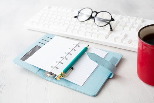 ノートパソコン、卓上カレンダー、スマホ、シャープペンシル、眼鏡。広げられたリングノートの上に無造作に置かれたカーネーション。コーヒーの入った赤のマグ。