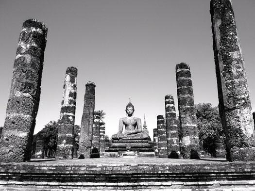 Das Bild ist schwarz-weiß. Es ist eine Buddhastatue auf einer Steinruine zu sehen. Links und rechts von ihm stehen jeweils fünf Steinsäulen.