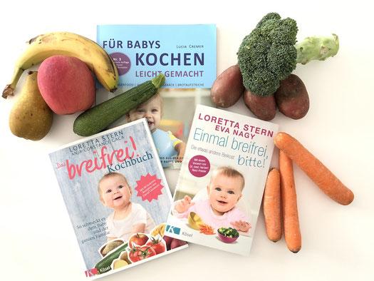 Bücher über die Beikosteinführung über Brei Baby-Led Weaning (BLW), Babybrei, Fingerfood, Familienessen, Essen für Kinder. Bücher liegen auf einem Tisch mit Karotten, Brokkoli, Kartoffeln, Banane, Apfel, Birne und Zucchini