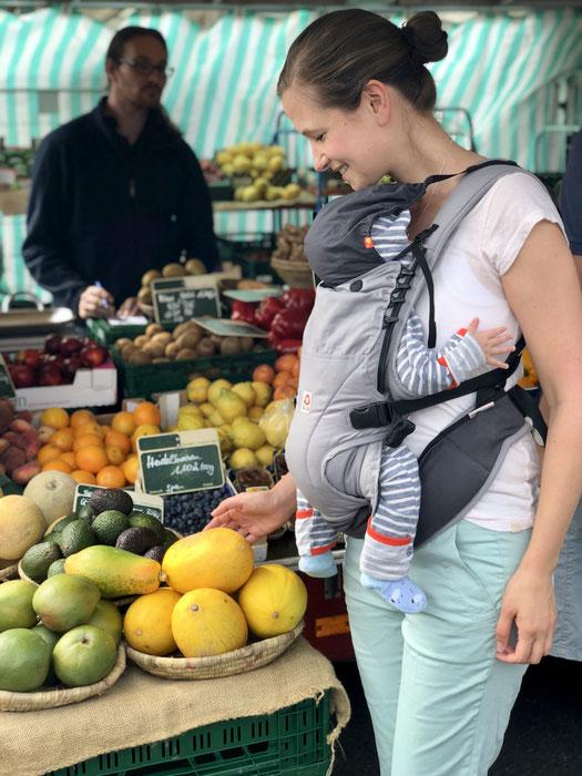 Auf dem Wochenmarkt einkaufen mit Baby für gesunde Ernährung in der Stillzeit. Frisches Obst.