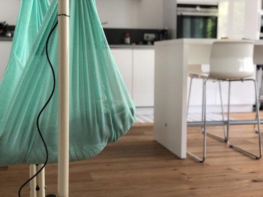 Federwiege steht auf Holzboden in weißer Küche mit Bartisch und Stühlen Baby macht Mittagsschlaf in der Wippe