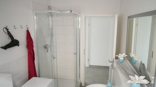 modernes Badezimmer mit Glasdusche und Waschmaschine