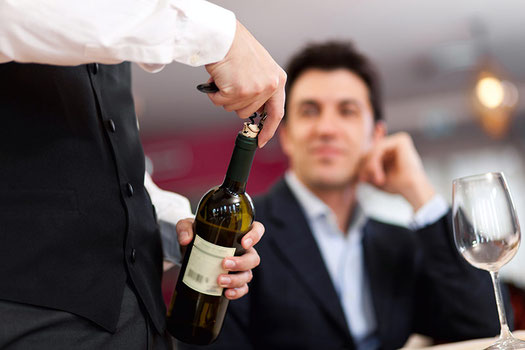 Kellner öffnet Flasche